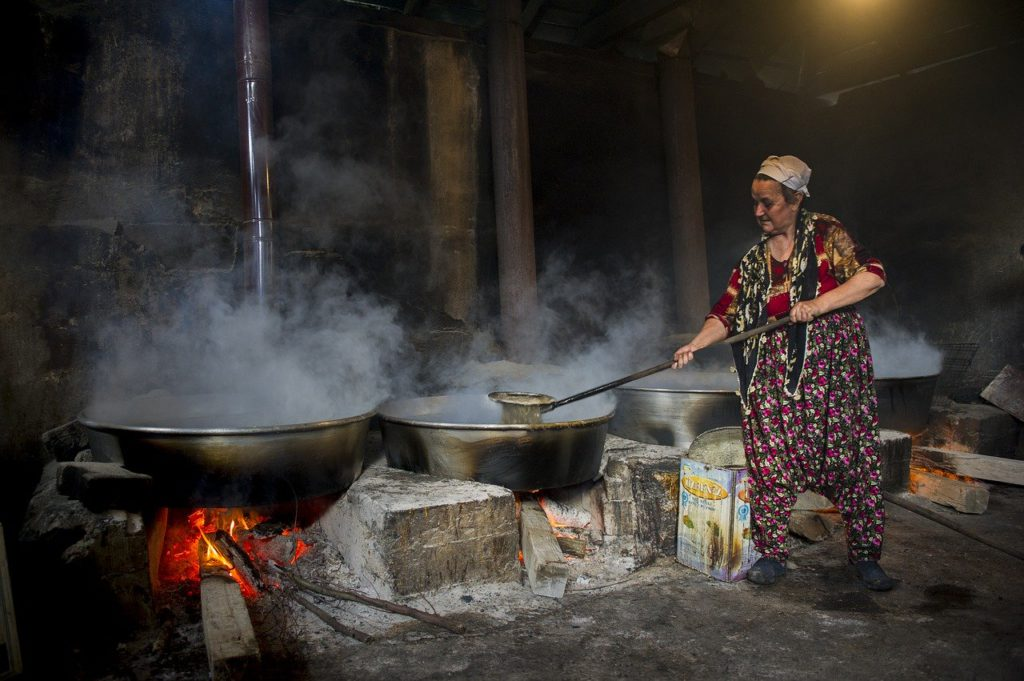 old woman making molasses by boiling cane sugar water